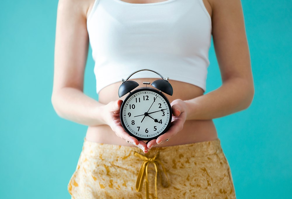 a woman holding a clock