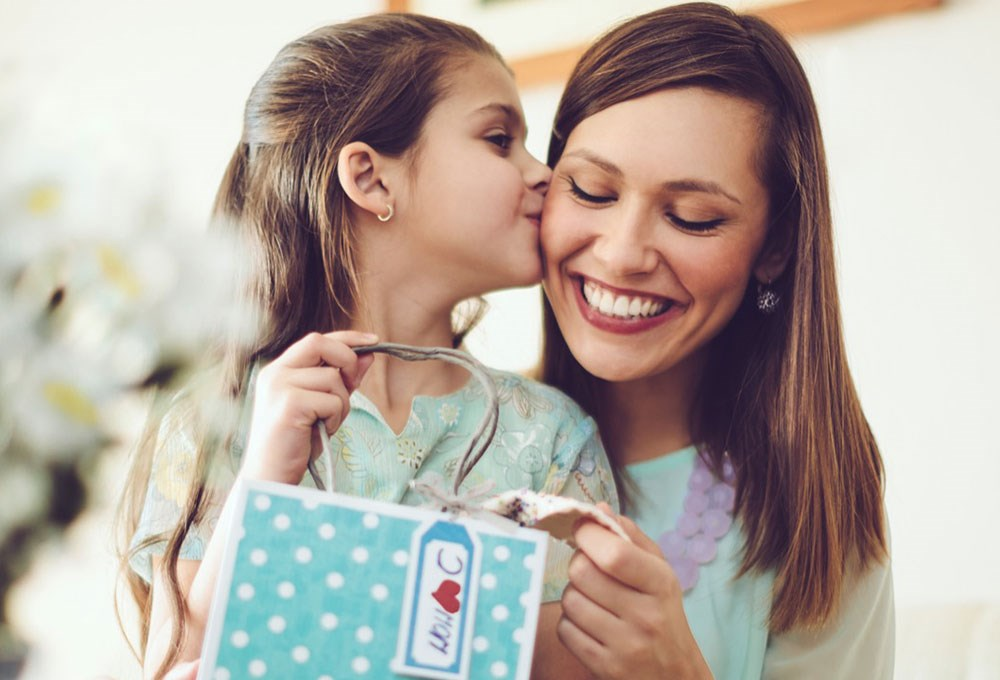 a couple of women smiling and looking at a card