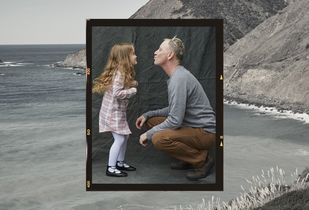 a man and a girl looking at a picture on a beach