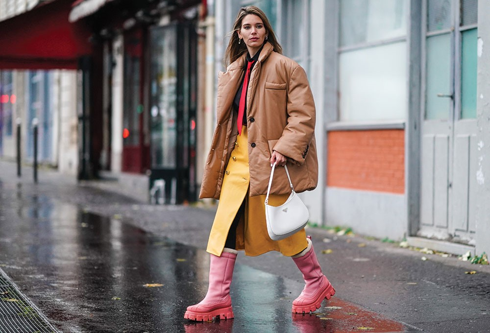 a person in a coat and boots walking in the rain