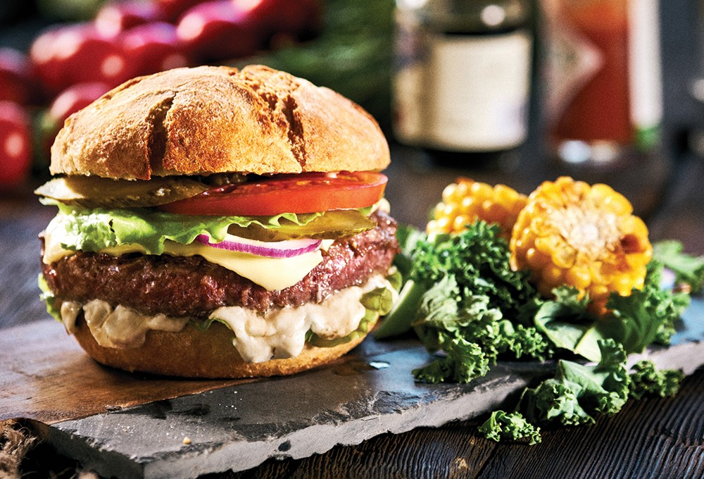 a burger with lettuce tomato and cheese