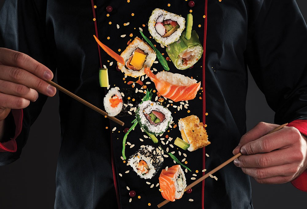 a person holding chopsticks with food on it
