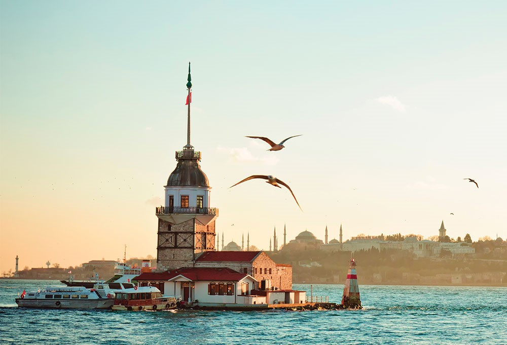 birds flying over a lighthouse with Maiden's Tower in the background