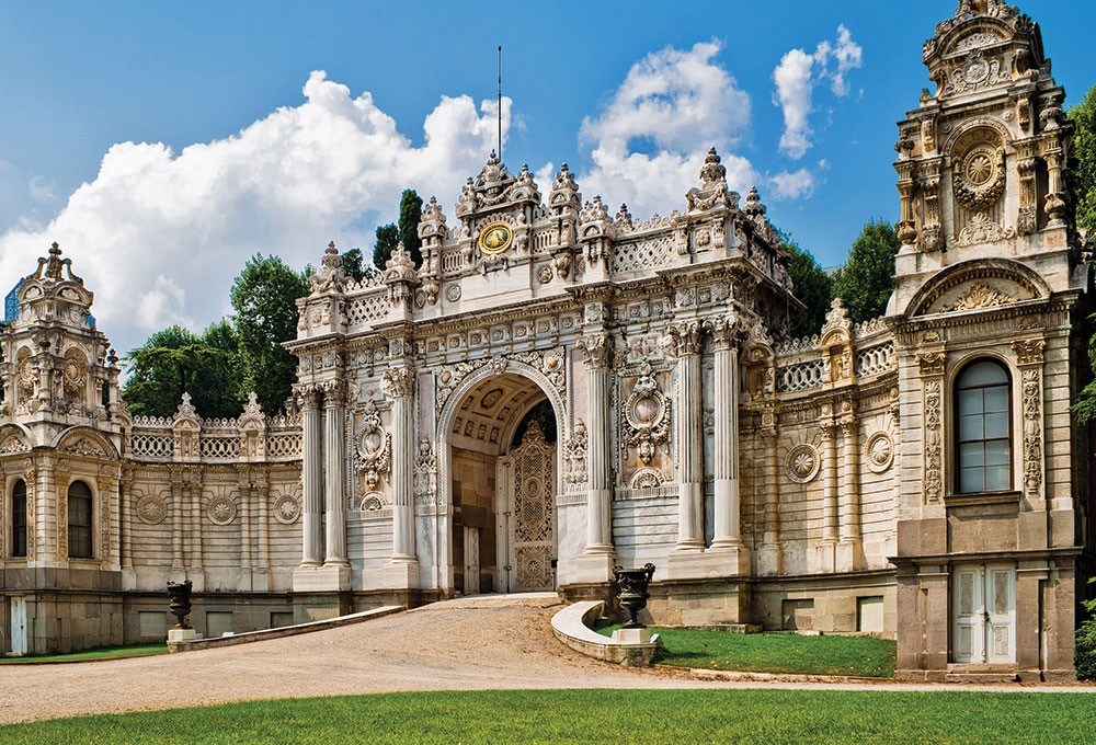 a large stone building with a large entrance with Dolmabahçe Palace in the background