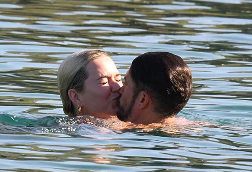 a man and woman kissing in water