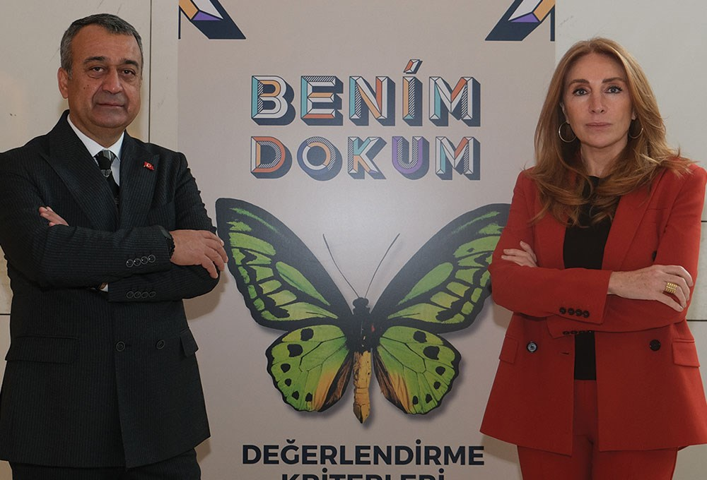 a man and a woman standing next to a poster