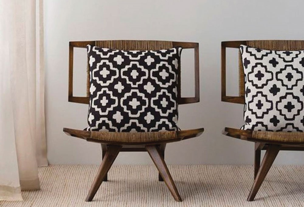 a couple of chairs with a decorative cushion